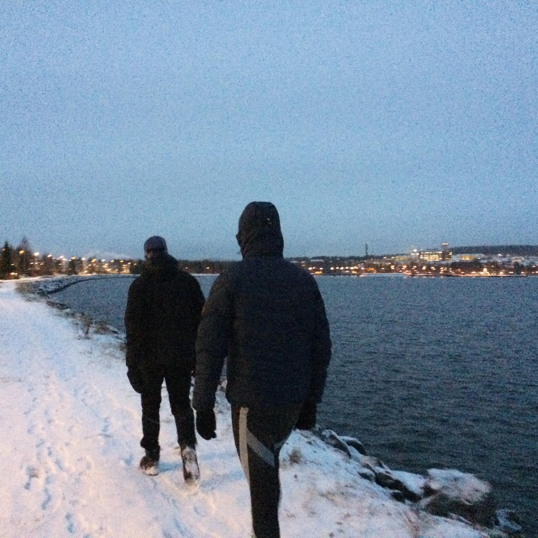 Bröderna Andersson går längs vattnet med Östersund stad som bakgrund